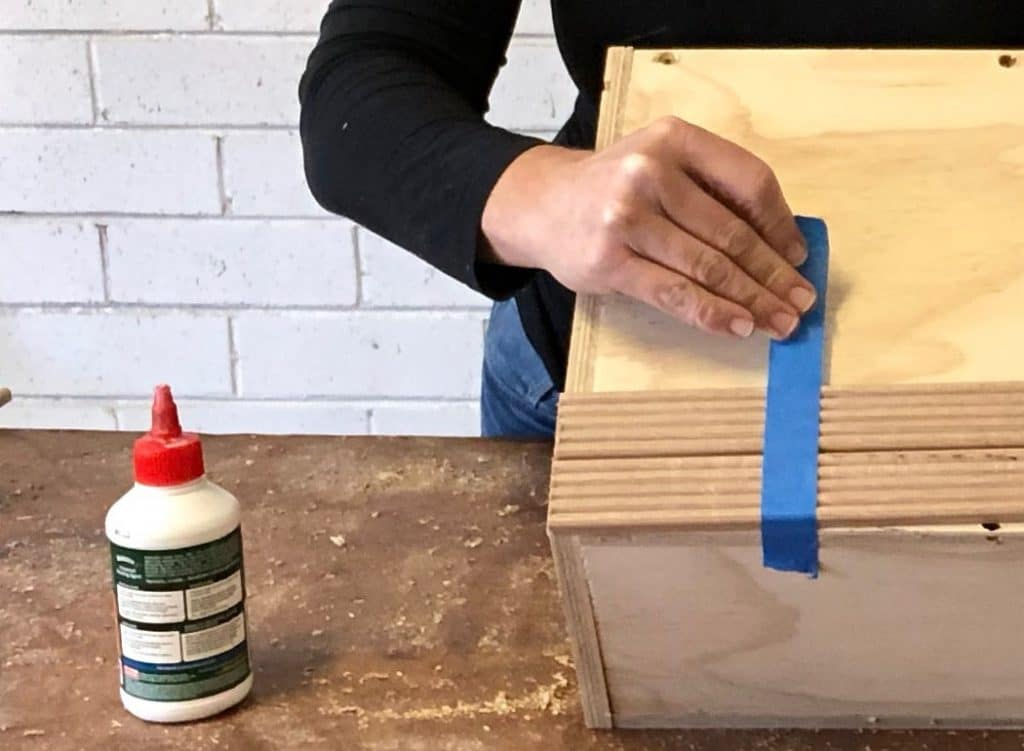 Start along one side, adding Bondcrete to each piece of cladding, positioning them to be flush with the top of the box. Pull the tape tight to hold the cladding while it dries.